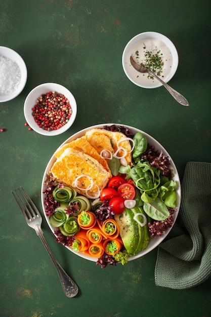 Кетогенная палео диетическая миска для обеда. сыр халуми, листья авокадо, морковь, огурец, листья салата Premium Фотографии