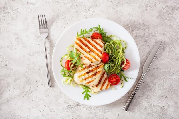 Кетогенный палео диетический обед. сыр халлуми, спирализованный цуккини с рукколой песто и помидорами Premium Фотографии