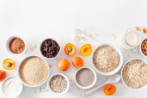 Вариаты из сырых злаков, фруктов и орехов на завтрак. хлопья овсяные и стальные порезать, ячмень, орех, чиа, абрикос. полезные ингредиенты Premium Фотографии
