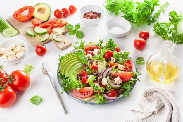 Салат из авокадо в греческом стиле с сыром фета, маслинами, огурцом, луком, салатом Premium Фотографии