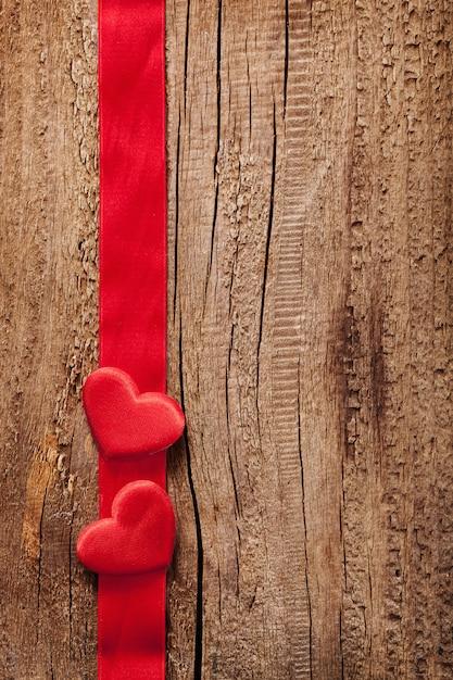 赤いハートとリボンフレームの木製の背景 Premium写真