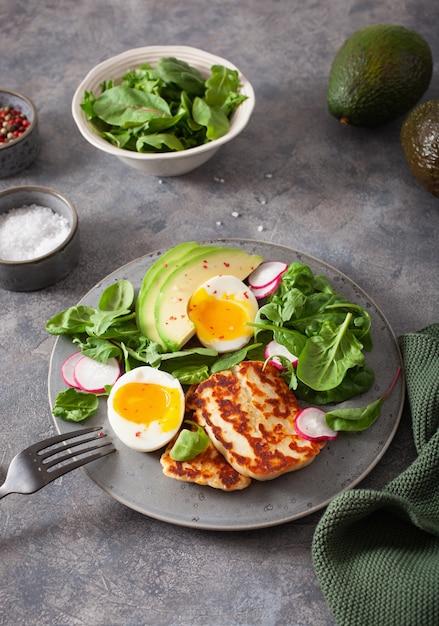 Здоровый кето палео диета завтрак: вареное яйцо, авокадо, сыр халлуми, листья салата Premium Фотографии