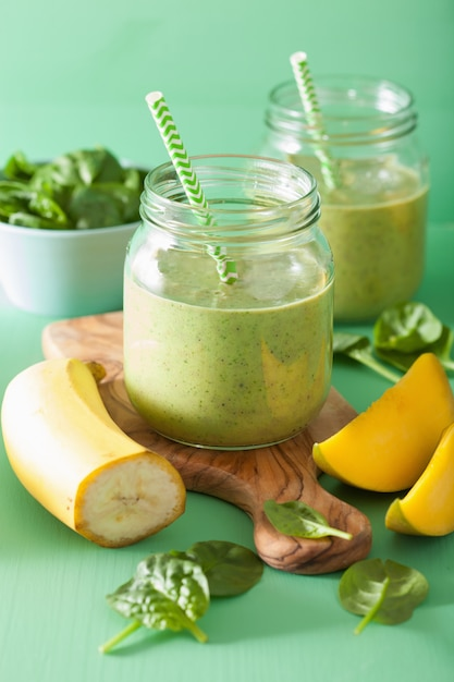 ガラスの瓶にほうれん草のマンゴーバナナと健康的な緑のスムージー Premium写真