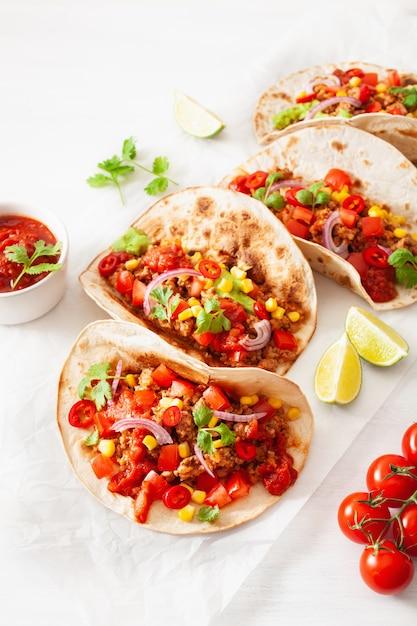 メキシコの牛肉と豚肉のタコス、サルサ、ワカモレ、野菜 Premium写真