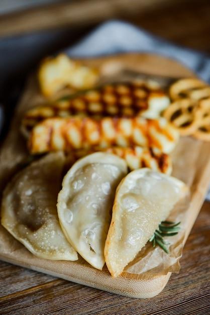 Жареный сыр халлуми и пельмени с розмарином на деревянной разделочной доске на деревянный стол с небольшими кренделями Premium Фотографии
