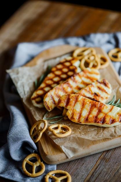 Жареный сыр халлуми с розмарином на деревянной разделочной доске на деревянный стол с небольшими кренделями Premium Фотографии