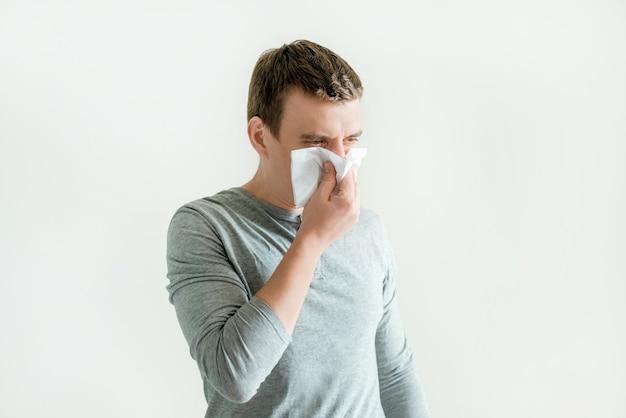 Молодой человек чихает в носовом платке, дует, вытирает насморк, респираторные инфекционные симптомы, симптомы гриппа и коронавируса Premium Фотографии