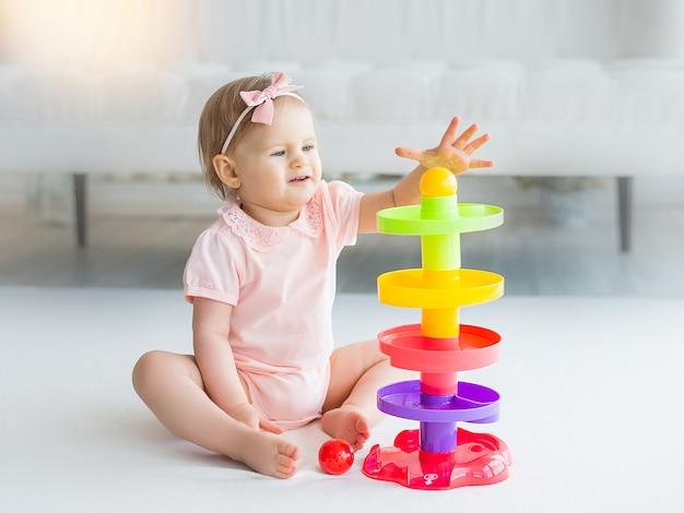 カラフルなおもちゃを自宅で遊ぶかわいい女の子 Premium写真