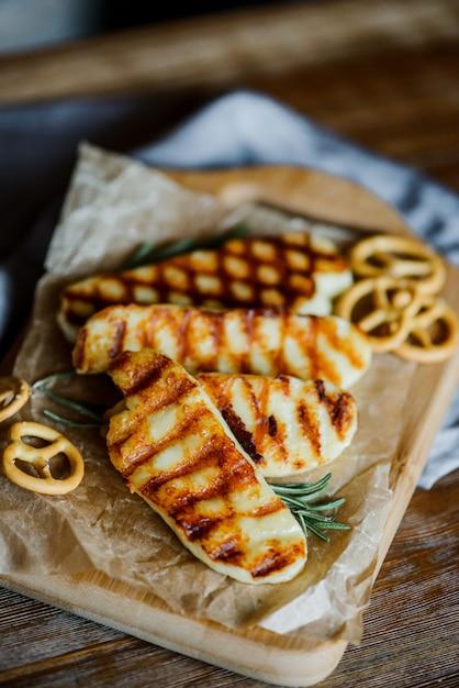 Жареный сыр халлуми с розмарином на деревянной разделочной доске с небольшими кренделями Premium Фотографии