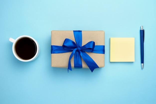 Подарочная коробка с голубой лентой лук чашку кофе и блокнот, изолированных на синем фоне. Premium Фотографии