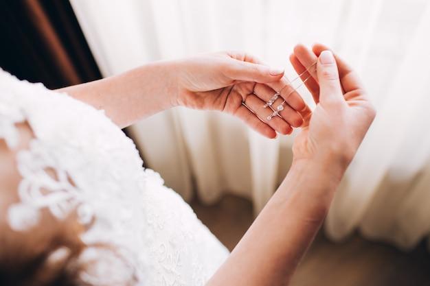 Платья подружки невесты серьги. девушка держит серьгу нежное утро невесты. реклама ювелирных изделий Premium Фотографии