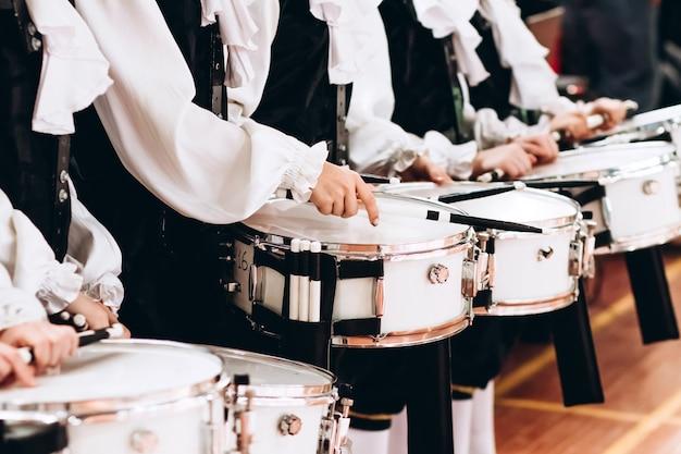 Крупный план рук барабанщика на параде. детский ансамбль в белых рубашках. белый новый малый барабан, белые палочки. концепция военного парада и марша. Premium Фотографии