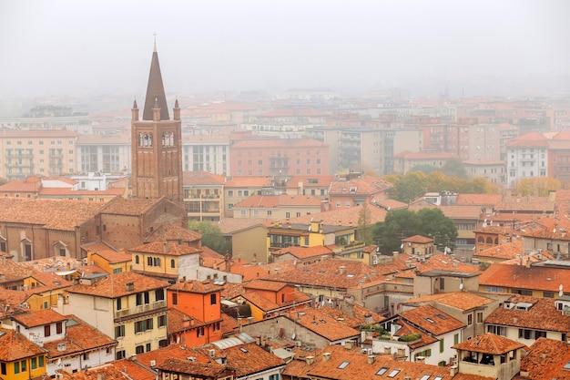 Взгляд на старом городке вероне в виде с воздуха, италии. туман выше в вероне. красные крыши средневекового города в италии Premium Фотографии