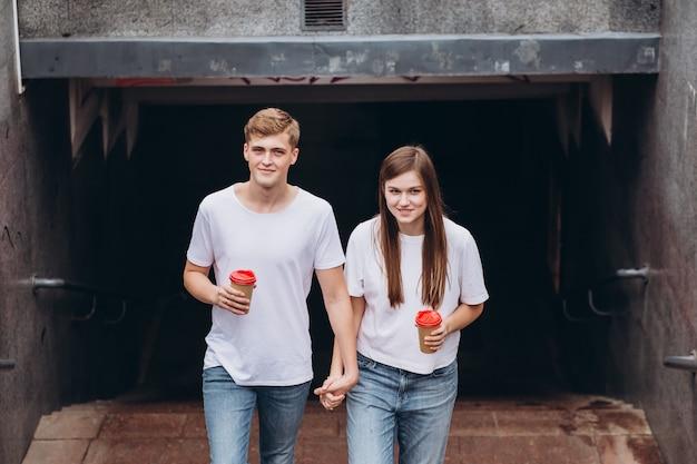 Счастливая молодая пара гуляет по улицам города и пьет кофе из картонной чашки. Premium Фотографии