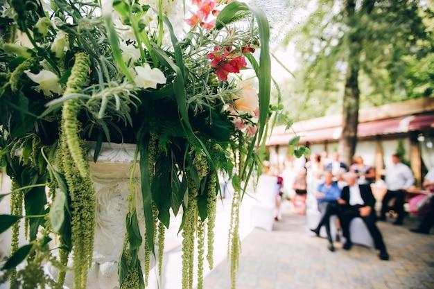 日陰の公園の美しい結婚式の写真ゾーン、白いスクリーン、花と装飾が施された台座。 Premium写真