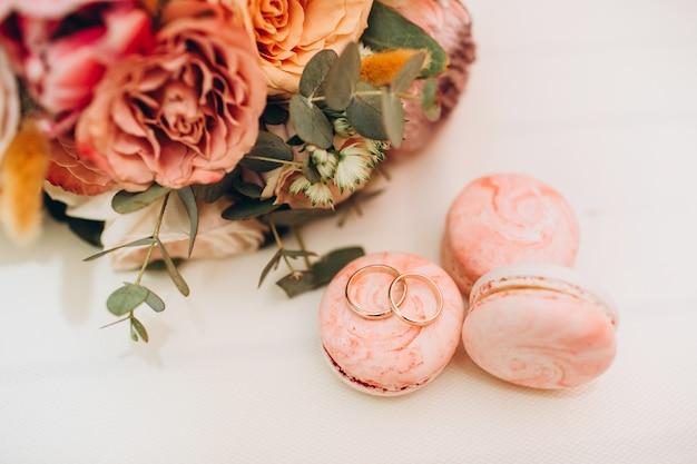 秋の色、結婚指輪、白いテーブルの上のマカロンのウェディングブーケ。 Premium写真