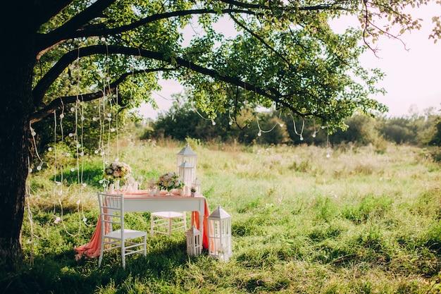 公園の夕日、ロマンチックな結婚式のディナーで美しく装飾されたお祝いテーブル。 Premium写真
