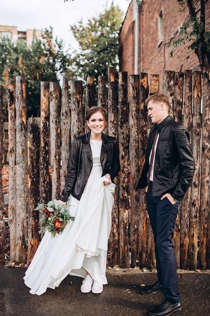 雨の後、若い幸せなカップルが街を歩いています。屋外の革のジャケットで新郎新婦。秋の結婚式。 Premium写真
