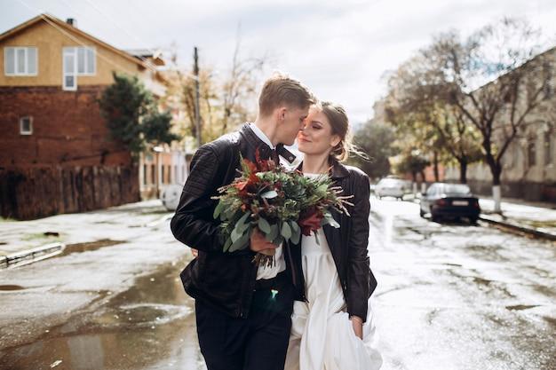 雨の後、若い幸せなカップルが街を歩いています。男と女のクローズアップの肖像画。屋外笑顔の愛情のあるカップル。市内の晴れた秋の日。 Premium写真