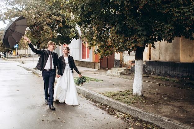 雨の後、若い幸せなカップルが街を歩いています。傘を持つ男女のクローズアップの肖像画。屋外笑顔の愛情のあるカップル。男が通りを歩いて傘を振る Premium写真