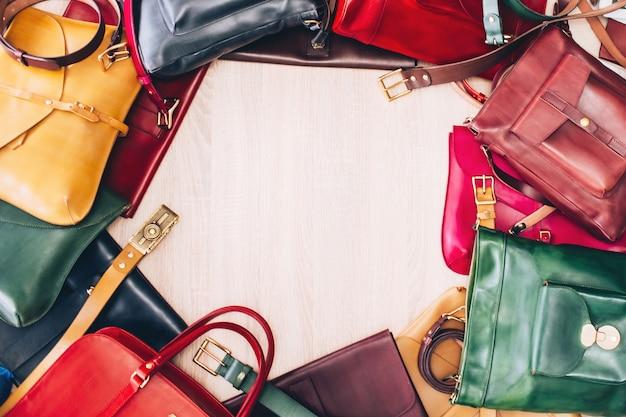 テーブルの上に並べられたカラフルな革のバッグ。バッグを持つテーブルの平面図です。革製品店。革のスーツケースブルー、レッド、イエロー、グリーン。 Premium写真