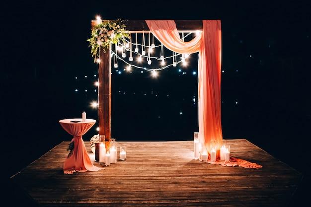 夜の結婚式。結婚式は夕方にアーチで飾られています。電球のガーランド。ガラスフラスコのキャンドル。 Premium写真