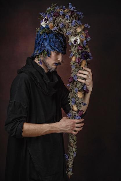 Человек с голубыми цветами на темной комнате Premium Фотографии