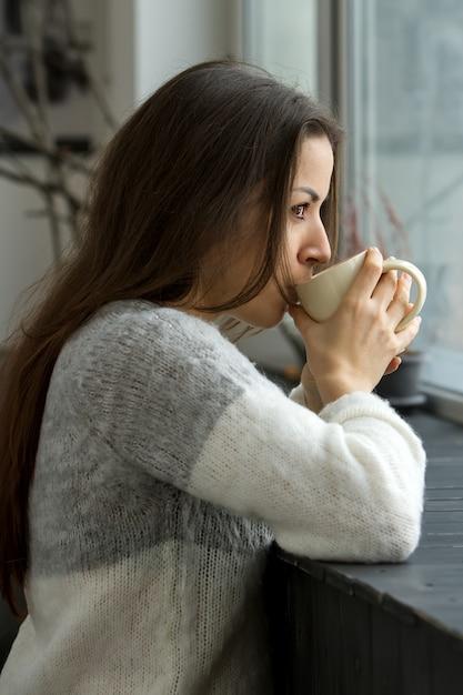 一杯のコーヒーを飲む家の女性 Premium写真