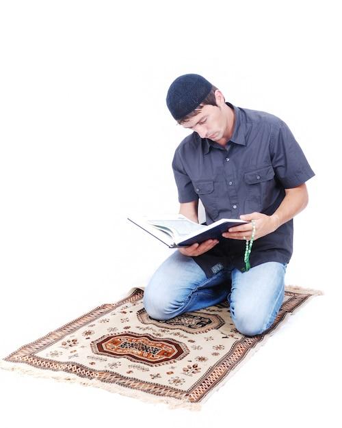 Мусульманин держит холли книгу коран и молится по традиции Premium Фотографии