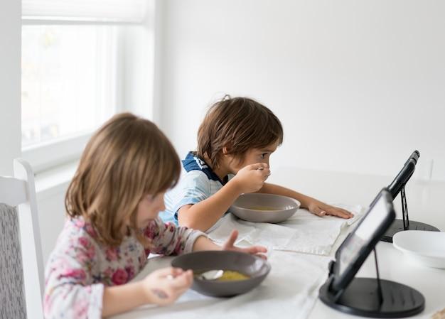 Дети в столовой едят и смотрят планшет Premium Фотографии