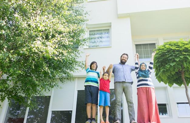 美しいモダンな家の前にイスラム教徒の家族 Premium写真