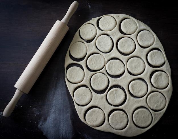 Стол с домашними пончиками во время процесса Premium Фотографии