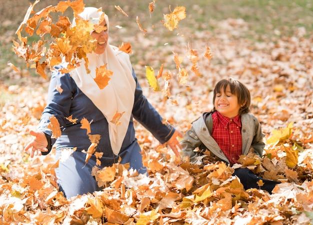 秋の息子とアラビアのイスラム教徒の母親を葉します。 Premium写真