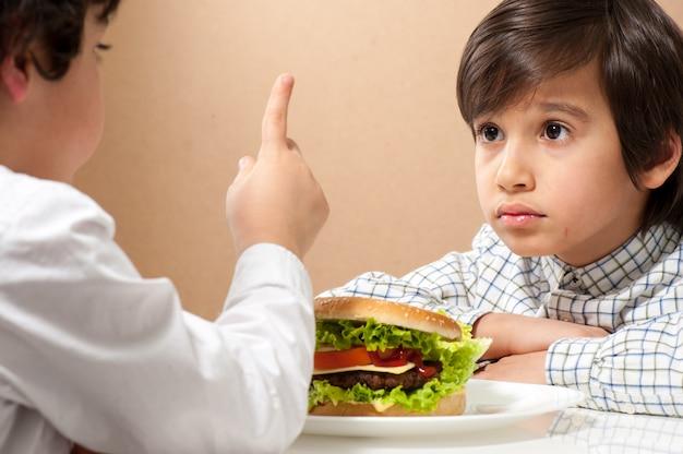 ハンバーガーを食べる子 Premium写真