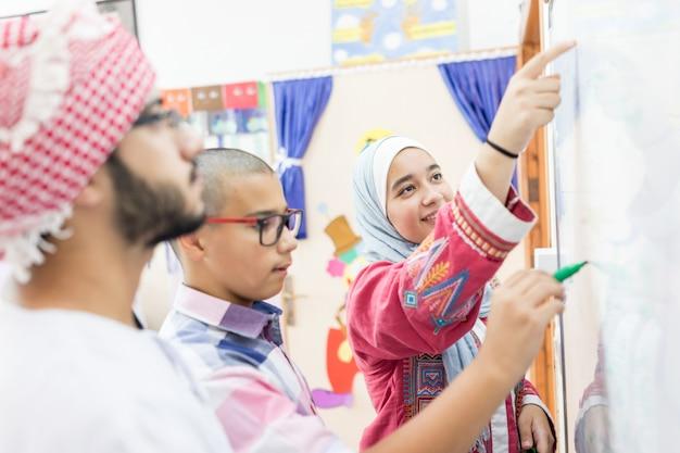 ホワイトボードで数学の質問を解くイスラム教徒のアラブの学生 Premium写真