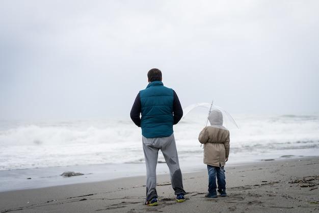 父と息子の冬のビーチで楽しんで Premium写真