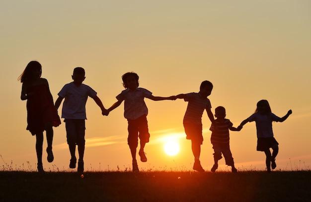 日没時の自然の中の幸せな人々のシルエット Premium写真