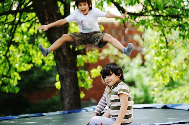 Счастливые дети, наслаждающиеся детством на батуте Premium Фотографии