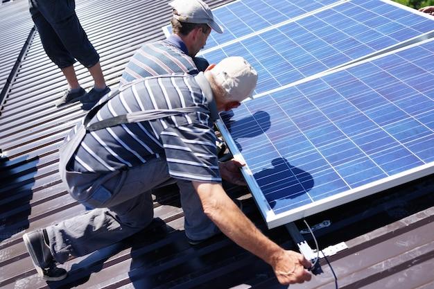 Человек, устанавливающий фотоэлектрические солнечные панели на солнечной энергии Premium Фотографии