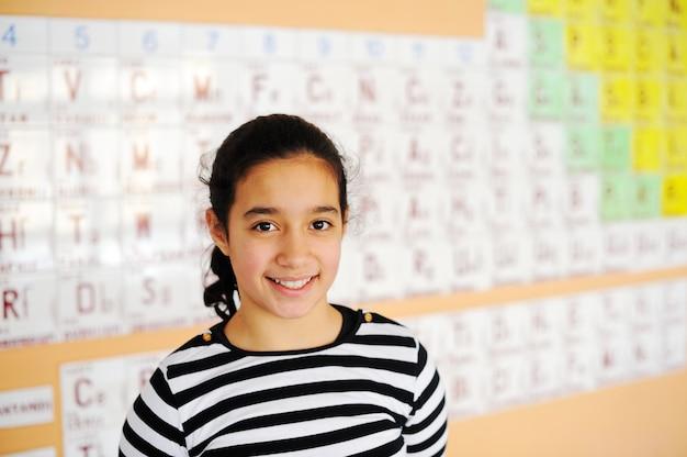 元素の周期表を持つクラスでかわいい素敵な学校の子供たち Premium写真