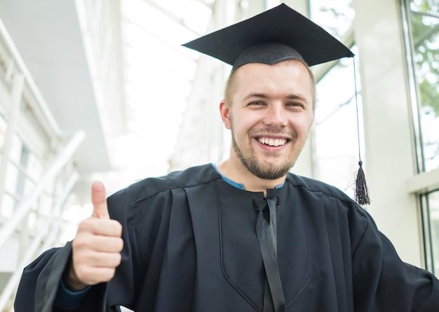黒の卒業ガウンで若い男子学生 Premium写真