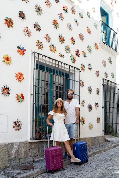 Счастливая пара в отпуске с чемоданами в андалузском городе Premium Фотографии