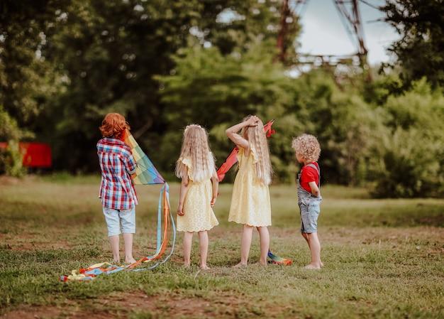 Маленькие дети играют с яркими воздушными змеями на зеленой поляне Premium Фотографии