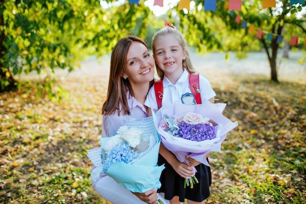 お母さんは花束を持ったかわいい娘を学校に見送ります Premium写真