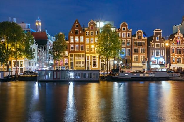 Ночной город амстердам канал с голландскими домами Premium Фотографии