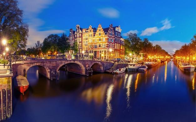 アムステルダムの運河と橋の街の夜景 Premium写真