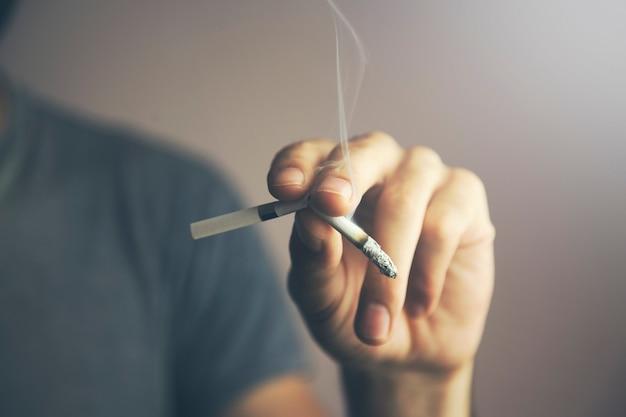 Рука молодого кавказского человека ломая зажженную сигарету с его пальцами Premium Фотографии