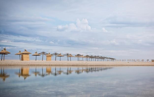 Соломенные зонтики стоят в ряд на песчаном морском побережье и отражаются в голубой воде. Premium Фотографии