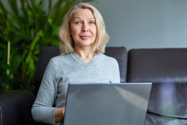 オフィスのソファーに座ってオンライン作業実業家。 Premium写真