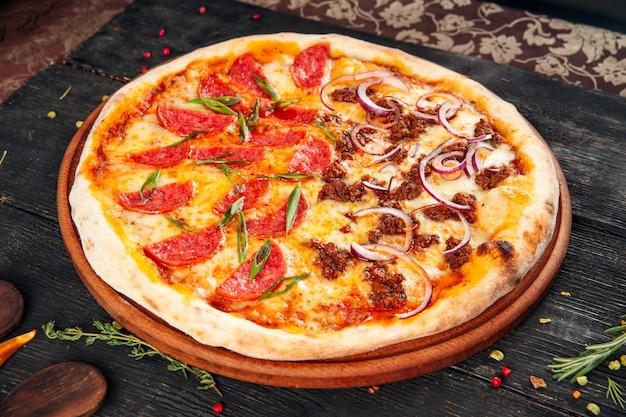 ピザソーセージの肉とタマネギの木製のテーブル Premium写真